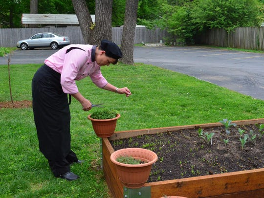 Denise LeBolt cuts herbs from the new garden that was