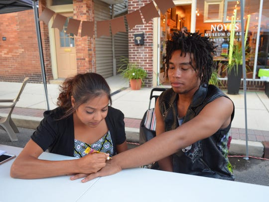Henna artist Ashlesha Parekh of Egg Harbor Township draws a henna tattoo on Sherode Jamison of Atlantic City during the New Jersey Fringe Festival in Hammonton on Friday.