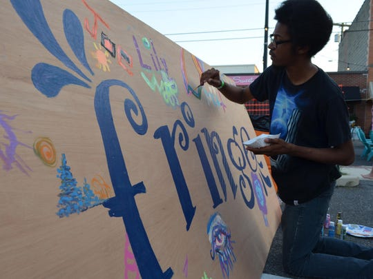 "New Jersey Fringe Festival visitors like Brandon Howard of Glassboro added their own artistic touch to a large ""fringe"" painting during the festival."