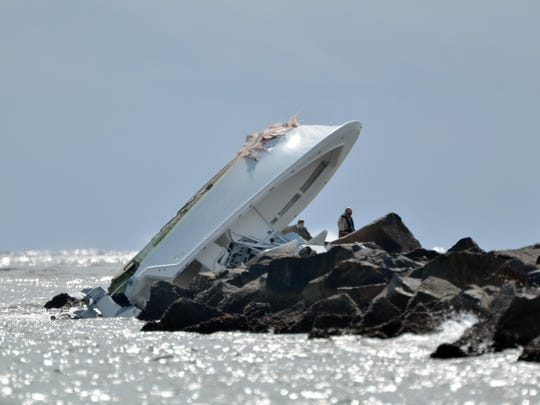 Investigators look at a boat overturned on a jetty Sunday off Miami Beach, Fla. Authorities said Miami Marlins starting pitcher Jose Fernandez was one of three people killed in the boat crash early Sunday morning. Fernandez was 24.