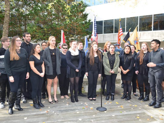 """Stockapella sing the national anthem on the steps of Campus Center and """"Amazing Grace"""" in Veterans Park during the Veterans Day program at Stockton University."""