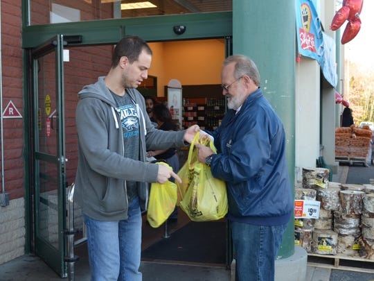 Robert Levin of Hammonton donates a turkey and some fixings to Robert Callaway of Egg Harbor Township, who volunteered to collect donations during the 16th annual Community Food Bank of New Jersey Turkey Drive.