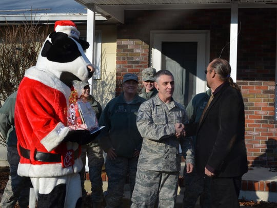 Master Sgt. Christopher LeConey of Egg Harbor Township is surrounded by members of his unit and the cow from Chick-Fil-A as he thanks Larry Stiteler of East Coast Roofing, Siding & Windows.