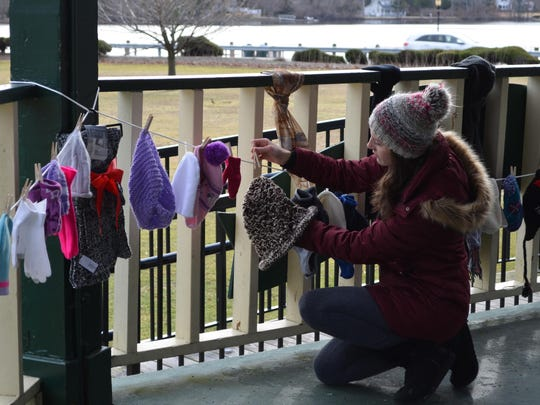 Hess School teacher Kim Smith pins a hat to a clothesline in the Gaskill Park gazebo for Cozy in the Cold.