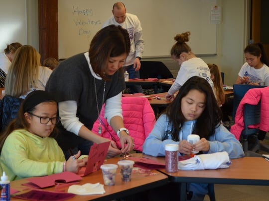 Susan Angulo helps her daughters Chloe Angulo, 10, and Sophie Angulo, 12, all of Cherry Hill, make Valentine's Day cards for seniors during the Stockton University MLK Day of Service.