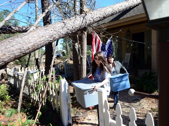 Linda Richardson, right, and daughter Breanna move boxes of personal items from their home that was damaged by the Jan. 21 tornado.