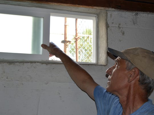 Charles Koehler of Charlie's Home Maintenance and Repair LLC in Vineland checks a basement window. Check seals around windows and be sure to only open them as weather permits. Photo/Jodi Streahle