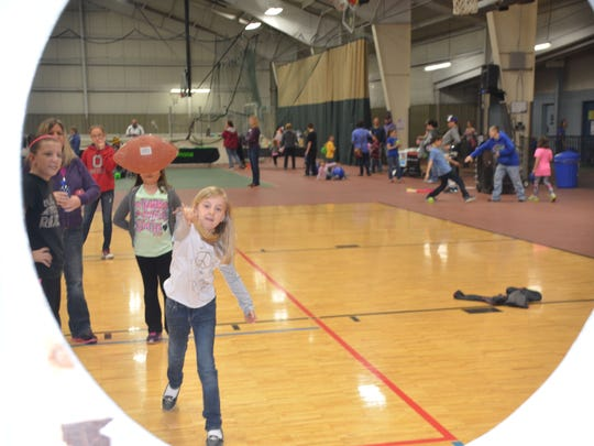 Mykelle Anders takes a shot at the football toss at the free Health Kids Day.