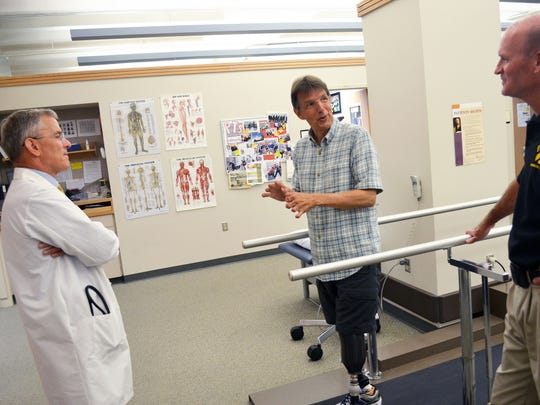 Dr. Tom Thomsen, left, and physical therapist Dick Evans, right, chat with Jeffery Ford on July 28 at University of Iowa Hospitals and Clinics. Ford, a well-known community volunteer, had both legs amputated below the knee and lost large portions of all 10 fingers after a battle with sepsis last year.