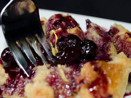 A piece of baked French toast covered in blueberry sauce from VKA Kitchen & Catering.