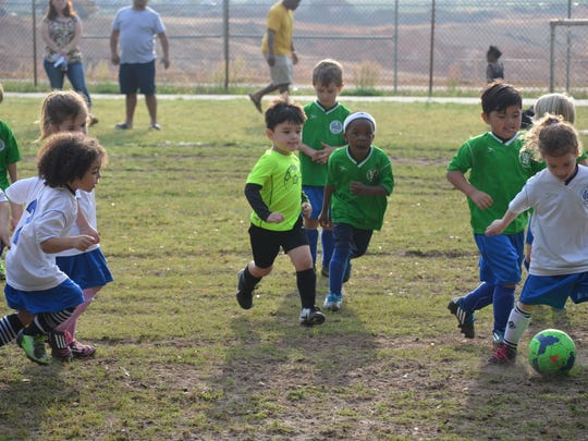 Jonah Alonzo, 4, center in bright green, chases after a soccer ball as part of the first day of the city-sponsored youth soccer league.