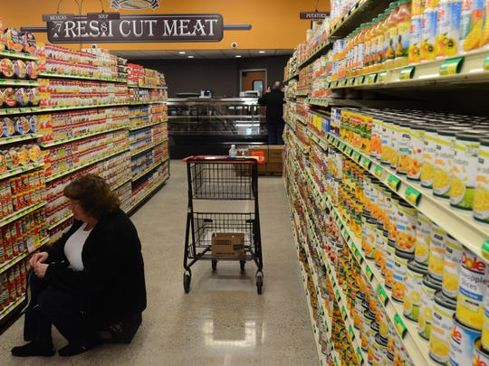 Sue Jackman, Fronney's Foods office assistant, helps to prepare the store for its opening on Monday by stocking shelves.