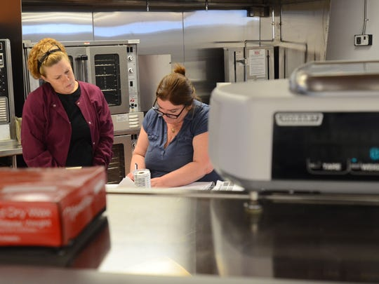 Laura Acheson and Linda Woodman, Fronney's Foods deli workers, plan recipes they will use in the deli once the store opens to the public on Monday.