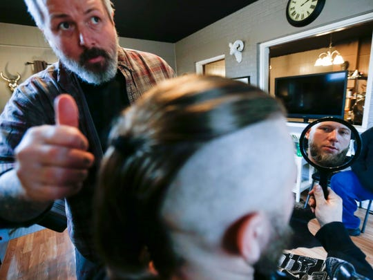 Lance Knight checks out his new haircut in a mirror