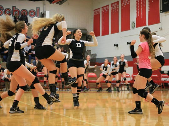 Daniella Barile (No. 13) and other Plymouth players celebrate scoring a point against Canton.