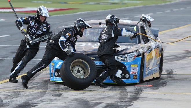 Crew members perform a pit stop on driver Kasey Kahne's car during qualifying for the NASCAR Sprint All-Star auto race at Charlotte Motor Speedway in Concord, N.C., Saturday, May 17, 2014.
