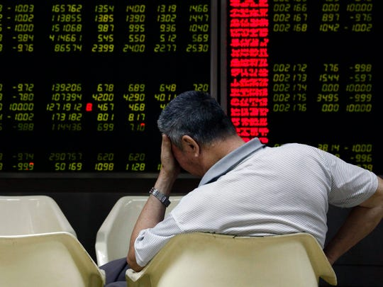 An investor reacts while monitoring stock data on an