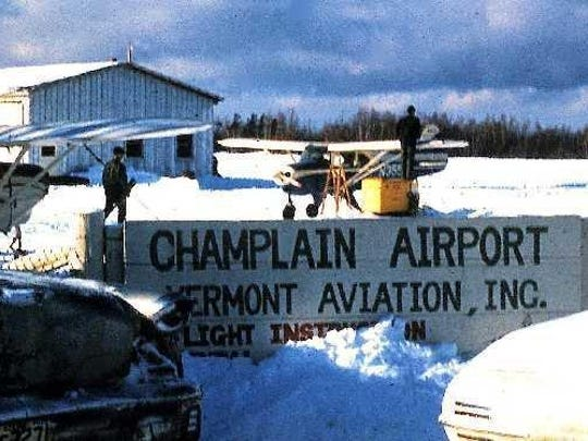 A 1961 photo of Champlain Airport shows a typically snowy scene, with three Pipers, a hangar and the airport sign.The building in the background was the main hanger with a heated shop on the right end.