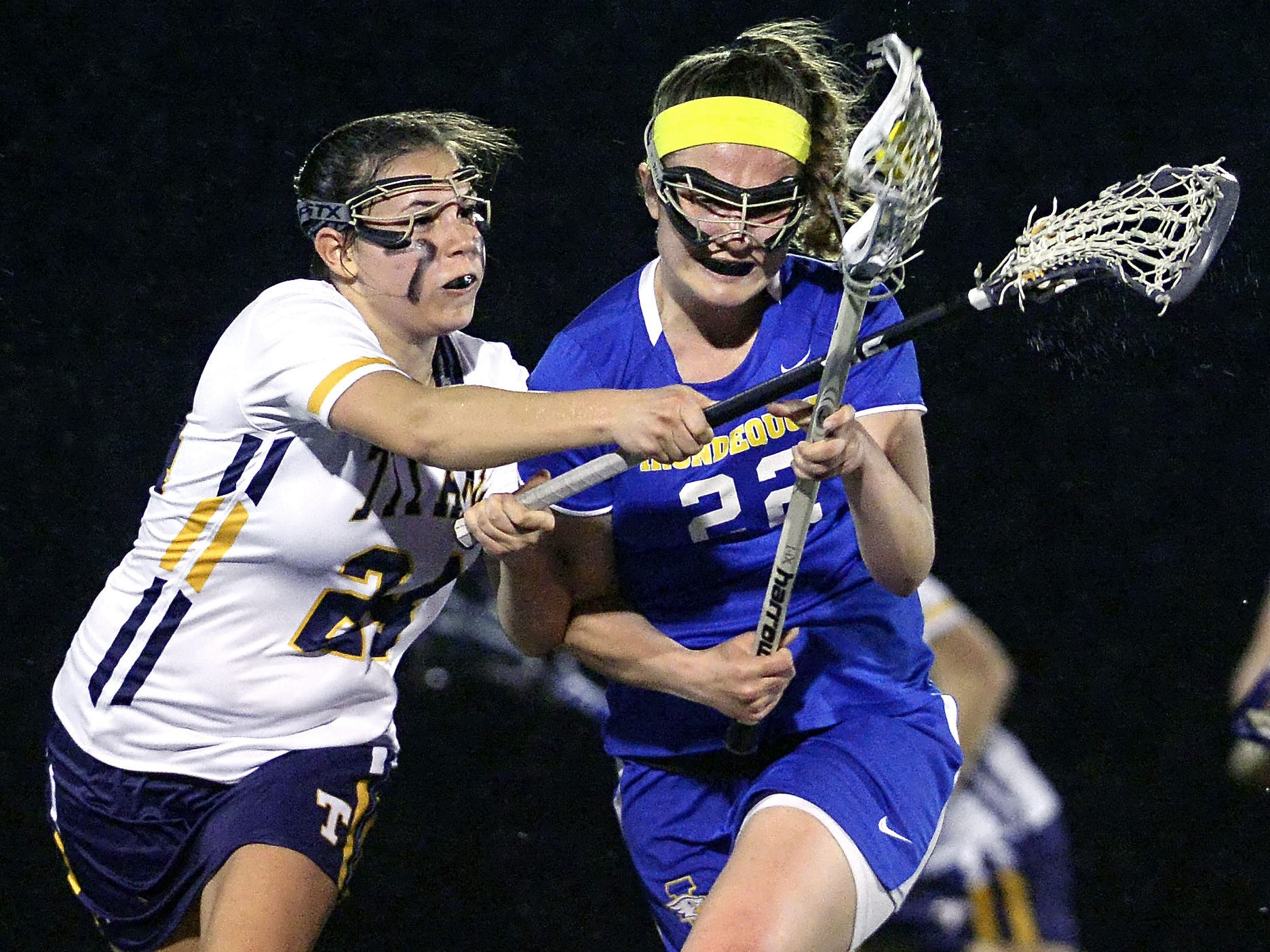 Webster Thomas' Emily Resnick, left, defends against Irondequoit's Katie Miller during a regular season game played at Webster Thomas High School on Monday, April 13, 2015.