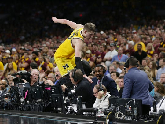 Michigan's Moritz Wagner jumps over press row, including