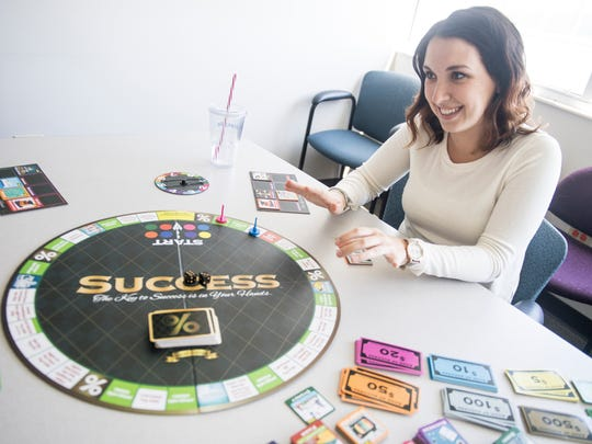 Knoxville Business Journal's Cortney Roark plays Success, a board game, on Tuesday, May 1, 2018.