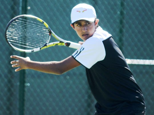 Northville's No. 1 singles player Janak Mukherji gets ready to uncoil for a forehand.