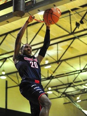 Comeaux's Xavier Ledet (20) dunks the ball during the first half of high school basketball game.