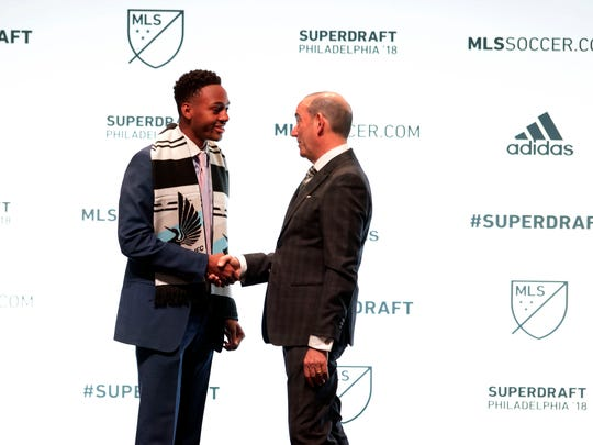 Mason Toye shakes hands with MLS commissioner Don Garber (right) after being selected number 7 overall by the Minnesota United FC in the 2018 MLS Super Draft at Pennsylvania Convention Center.