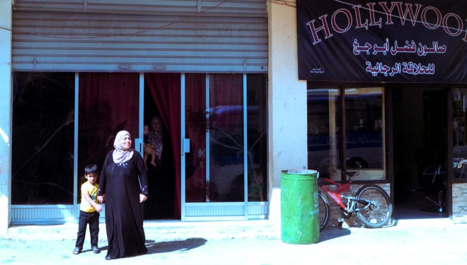 Gharam Al Shuqi's stands in front of her makeshift home in Ghazze. She lives with her sister and sister-in-law and their 11 children in a windowless space once used as a shop or garage.