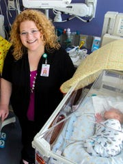 Dawn Schwartz, director of the neonatal intensive care unit at Mercy Medical Center, watches over NICU patients Zaidee and Huxlee of Diagonal. The daughters of Lisa Stull spent the first few weeks of their lives at Mercy.