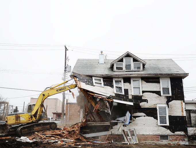 Construction crews work to tear down houses to make room for new townhomes on Thursday, April 3, 2014,  along 2nd Avenue across from Sunshine Foods in Sioux Falls. (Joe Ahlquist / Argus Leader)