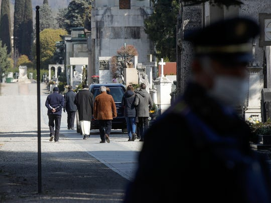 FILE - In this Tuesday, March 17, 2020. filer, relatives walk behind a hearse carrying a coffin inside the Monumentale cemetery, in Bergamo, the heart of the hardest-hit province in Italy's hardest-hit region of Lombardy, Italy. For most people, the new coronavirus causes only mild or moderate symptoms. For some it can cause more severe illness, especially in older adults and people with existing health problems. (AP Photo/Luca Bruno, File)
