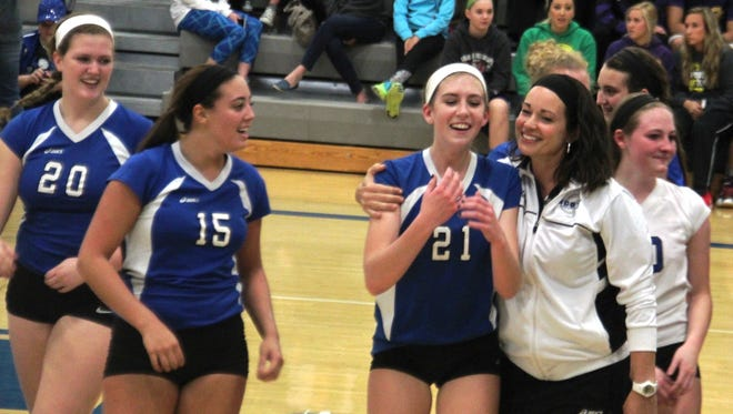 Scott head coach Andrea Sullivan (right) hugs junior Jessica Tapp (21) after the match as senior Jenna Trimpe (15), Kimberly Davis (20) and Allie Bishop (10, white shirt) also celebrate. Scott beat Campbell County 3-0 in the 10th Region volleyball final Oct. 30, 2014 at Scott HS in Taylor Mill.