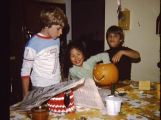 A young Kim Pegula, center, carving pumpkins with her brothers.