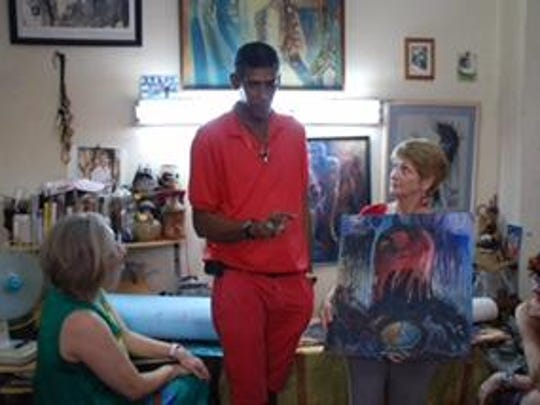 Artist Cuban artist Francisco Gordillo Arredondo Baba Oñi talks with a group of Brevard art enthusiasts who visited his home during a 2014 cultural trip organized by the Foosaner Art Museum.