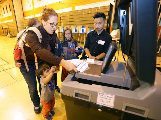 Emily Schoenfelder feeds her ballot after voting at