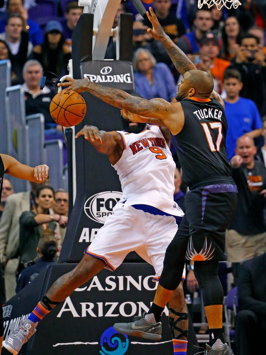 Phoenix Suns forward P.J. Tucker (17) makes a defensive stop against New York Knicks center Kyle O'Quinn (9) during overtime of an NBA basketball game Tuesday, Dec. 13, 2016, in Phoenix. The Suns won 113-111. (AP Photo/Ross D. Franklin)