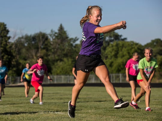 Allison Schunk, 17, does switch lunges with dozens of others Thursday, August 5, 2016 at St. Clair High School.