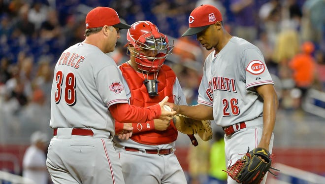 Starting pitcher Raisel Iglesias (right) is taken out of the game by manager Bryan Price (left) during the fifth inning.