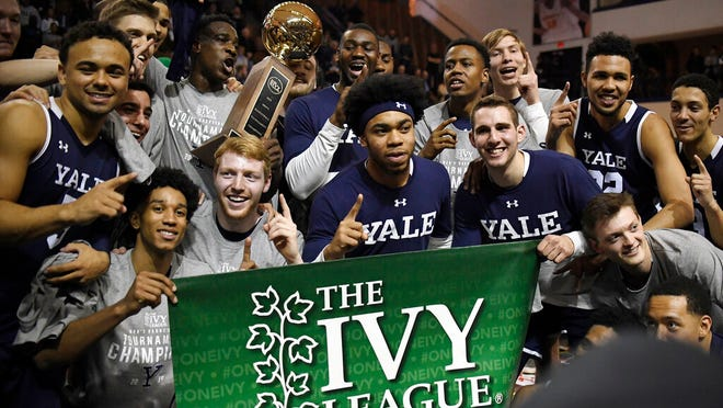FILE - In this March 17, 2019, file photo, Yale players pose for a photograph with the championship trophy after defeating Harvard in an NCAA college basketball game for the Ivy League championship at Yale University in New Haven, Conn.  The Ivy League on Tuesday, March 10, 2020, canceled its men's and women's basketball tournaments because of concerns about the spread of coronavirus. The four-team tournaments were scheduled to be played Friday through Sunday at Lavietes Pavilion in Cambridge. The Ivy League instead will award its automatic NCAA Tournament bids to the regular-season champions, the Princeton women and Yale men.