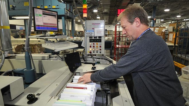 This is a December 2011 file photo of mail handler James Doud, sorting mail at the U.S. Postal Service's General Mail Facility on East 38th Street in Erie.