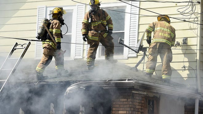 Erie firefighters battle a house fire March 27, 2020, at 642 W. 21st St. in Erie. Angel C. Gomez-Hernandez, 34, has been charged with arson and other counts in the incident.