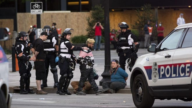"""Marisa """"Reese"""" Digati, seated, is detained by police during protests in Downtown Columbus on Sunday, May 31."""