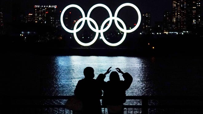 In this Dec. 1, 2020, file photo, a man and a woman look at the Olympic rings float in the water in the Odaiba section in Tokyo.