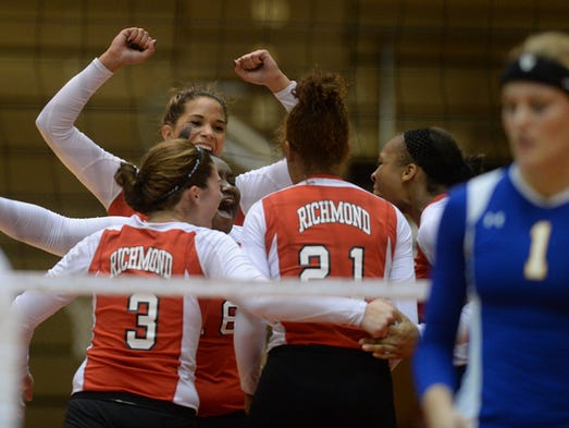 Richmond volleyball players celebrate a point during a volleyball match against Greenfield-Central in the Tiernan Center, Wednesday, Aug. 27, 2014.