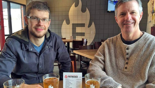 Marc Bailey, left, and his father, Clint, sample beer at Firetrucker Brewery in Ankeny as part of their statewide father-son tour of all 73 breweries in Iowa.