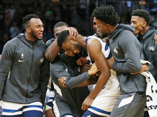 Minnesota Timberwolves' Andrew Wiggins (22) is swarmed by teammates after his third straight 3-pointer against the Miami Heat in the second half of an NBA basketball game, Sunday, Oct. 27, 2019, in Minneapolis. The Timberwolves won 116-109. Wiggins had 25 points. (AP Photo/Jim Mone)