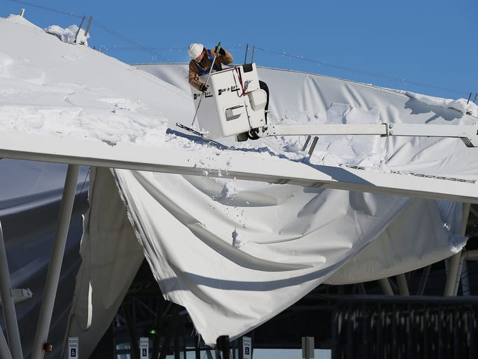 Workers for the Indianapolis Airport Authority and airport fire department secure and survey the damage after a section of the canopy in the parking garage collapsed under the pressure of heavy ice and snow Tuesday morning.