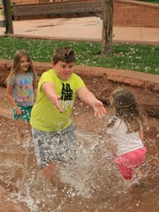 Peyton, Hudson and Paisley Larsen splash in the creek Thursday at St. George Town Square while on vacation from Kaysville.