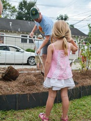 James Troyanowski plants a persimmon tree while his daughter, Clara, watches during the groundbreaking ceremony at the inaugural Victory Garden Festival. The Victory Garden was a long-time dream of Jillian Johnson, who was killed July 23 in the Grand 16 Theatre shooting.